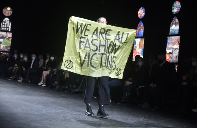 фото активистки с плакатом - Мы все жертвы моды